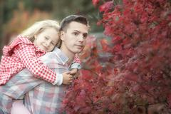 Little adorable girl with dad in autumn park at warm day Stock Photos