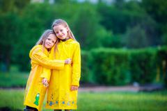 Funny cute toddler girls wearing waterproof coat playing outdoors by rainy and Stock Photos