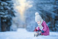 Adorable little girl with flashlight in frozen winter on Christmas outdoors Stock Photos