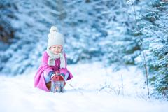 Little girl with flashlight and candle in winter day outdoors - stock photo