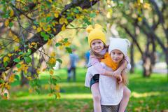Little adorable girls outdoors at warm sunny autumn day - stock photo