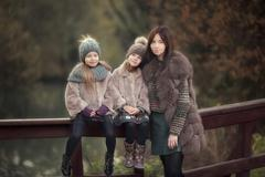 Adorable little girls with mother in autumn park outdoors - stock photo