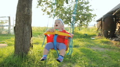 Cute baby boy playing on swing in summer garden. Swings are attached to the tree Stock Footage