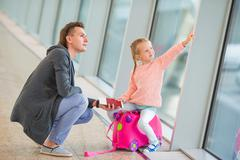 Happy family with luggage and boarding pass at airport waiting for boarding Stock Photos