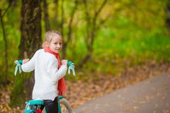 Adorable girl riding a bike at beautiful autumn day outdoors - stock photo