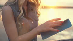 Beautiful girl in glasses using tablet or ebook on the background of sunset in - stock footage