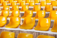 Stone steps with yellow plastic seats. Empty stools without people. Concept p - stock photo