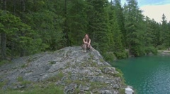 Aerial view of the woman sits on a cliff near Lago di Braies, Italy Stock Footage
