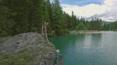 Aerial view of the woman stands on a cliff near Lago di Braies, Italy Stock Footage