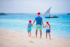Happy family in Santa Hats on summer vacation. Christmas holidays with young Kuvituskuvat