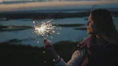 Beautiful young woman stands on a high hill with sparkler at sunset in slow Stock Footage