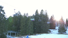 Cable car above ski track in ski resort. Sunny day. Solar glare through trees. - stock footage