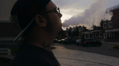 Young Man Stands On Street And Smoke E-Cigarette At Sunset. Vape. Slow-Mo. - stock footage