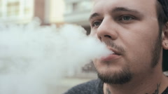 Young Man Smoke E-Cigarette On The Street. Vape. Slow-Mo. Stock Footage
