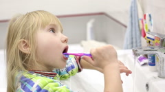Close up. Little girl brushing her teeth before a bedtime in the bathroom. Stock Footage