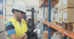 Tracking shot if a Logistics person working in a warehouse Stock Footage