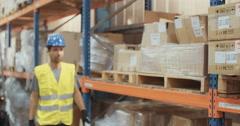 Logistics man wearing blue helmet working in warehouse Stock Footage
