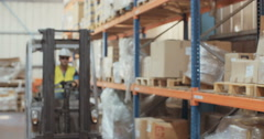 Slow motion shot of a Logistics worker getting off a forklift and marking items Stock Footage