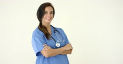 Woman in scrubs crosses arms and smiles at camera Stock Footage