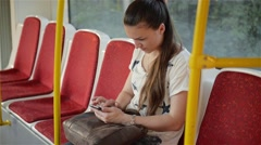 Beautiful young woman travelling in urban transport and using her mobile phone Stock Footage
