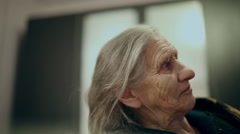 Profile of the face of an old woman. Grandmother watching TV and blinking eyes. Stock Footage