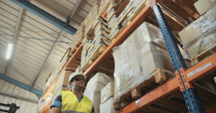 Low angle slow motion shot of a logistics man walking in a warehouse - stock footage
