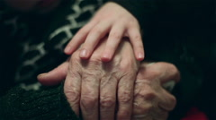 Hand of a little girl fondling old  hands of grandmother with love. Arkistovideo