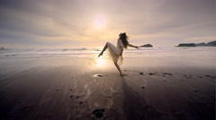 Young woman dancing on beach at sunset Port Orford, OR Stock Footage