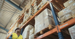 Low angle tracking shot of a worker marking items in a warehouse - stock footage