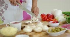 Housewife preparing dinner slicing fresh mushrooms Stock Footage