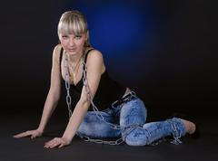 Sexy blonde in chains over black background - stock photo