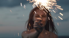 Romantic young woman stands on a high hill and holding Sparkler at dusk Stock Footage