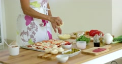 Woman preparing a homemade pizza in the kitchen Stock Footage