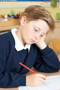 Bored Male Elementary School Pupil At Desk - stock photo