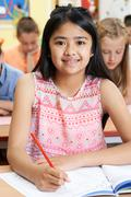 Female Elementary School Pupil Working At Desk Stock Photos