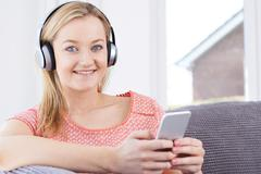 Woman Streams Music From Mobile Phone To Wireless Headphones Stock Photos
