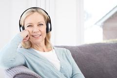 Mature Woman Listening To Music On Wireless Headphones Stock Photos