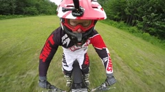 dirt biker rider cool slow motion in green pasture - stock footage