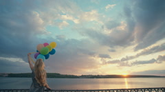 Woman in a happy dream flying in the sky lifted by helium balloons. RAW video Stock Footage