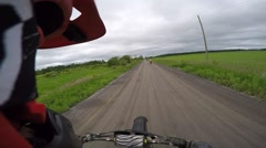 Dirtbike rider wheelie down dirt road with friends Stock Footage