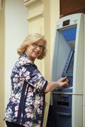 Mature blonde woman with credit card in hand near ATM Stock Photos