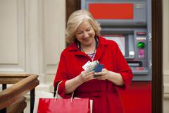 Mature blonde woman with shopping bags on the background of the ATM Stock Photos