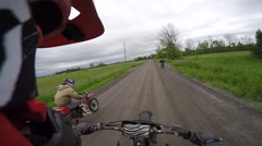 Dirtbike riders driving down dirt road Stock Footage