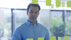 4K Male business colleagues brainstorming for ideas with sticky notes in office Stock Footage