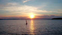 Drone video of sailboat crossing water during sunset Stock Footage