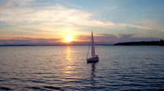 Aerial view of sailboat floating on water by sunset Stock Footage