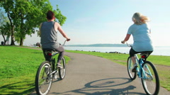 Couple rides bikes by Seattle waterfront Stock Footage