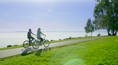 Couple rides bikes by Seattle waterfront 6 Stock Footage