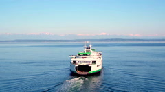 Boat crosses water towards Seattle mountains under blue sky 3 - stock footage