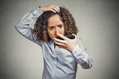 Shocked funny looking young woman, surprised she is losing hair Stock Photos